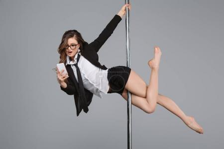 Photo for Young businesswoman in eyeglasses using smartphone and exercising with pole on grey - Royalty Free Image