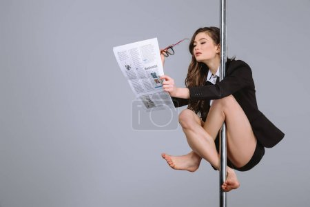 young businesswoman holding eyeglasses and reading newspaper while hanging on pole on grey
