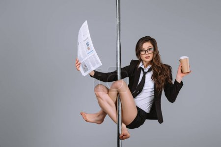 Photo for Young businesswoman in eyeglasses holding newspaper and coffee to go, hanging on pole and looking at camera on grey - Royalty Free Image