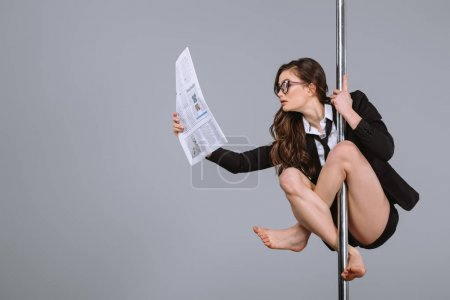 young businesswoman in eyeglasses hanging on pole and reading newspaper on grey