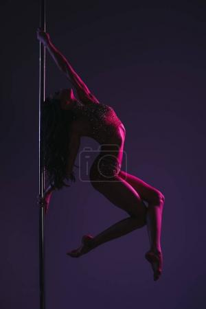 Photo for Side view of athletic flexible girl exercising with pole on blue - Royalty Free Image