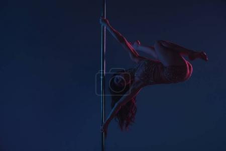 Photo for Full length view of athletic flexible young woman dancing with pole on blue - Royalty Free Image
