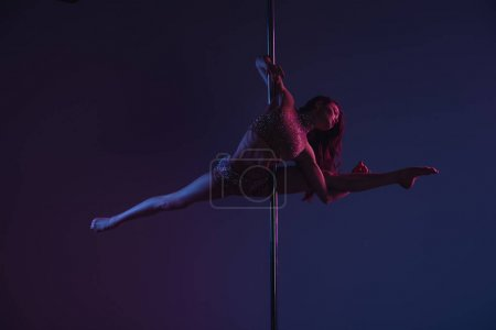 full length view of beautiful flexible girl dancing with pole on blue