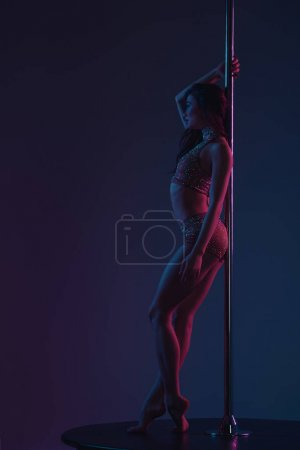 Photo for Side view of sporty seductive girl leaning at pole and looking away on blue - Royalty Free Image