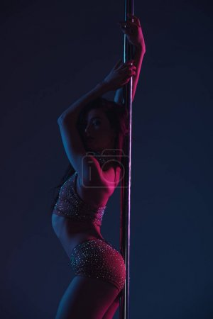 beautiful seductive young woman posing with pole on blue