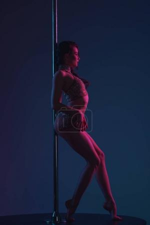 side view of seductive young woman leaning at pole and looking away on blue