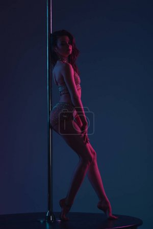 Photo for Side view of attractive flexible female dancer leaning at pole on blue - Royalty Free Image