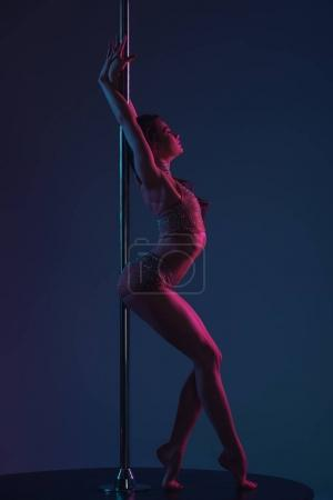 Photo for Side view of seductive young female dancer leaning at pole on blue - Royalty Free Image