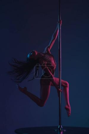 full length view of beautiful sensual young woman dancing with pole on blue
