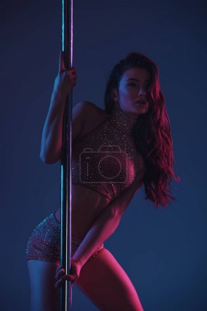 beautiful seductive girl dancing with pole on blue