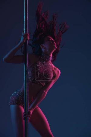 Photo for Beautiful seductive young woman dancing with pole on blue - Royalty Free Image