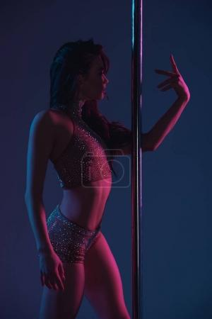 beautiful sensual young woman dancing with pole on blue