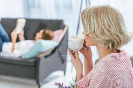 blonde woman drinking coffee while her friend relaxing behind