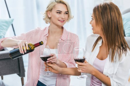 attractive smiling women with red wine spending time together