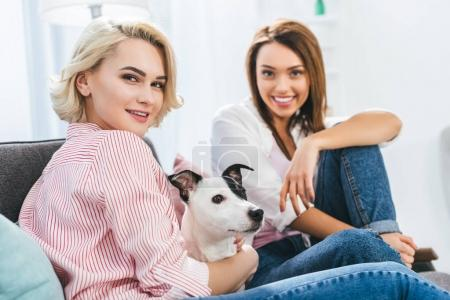beautiful smiling girls with jack russell terrier dog at home