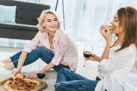beautiful happy girls drinking red wine and eating pizza together