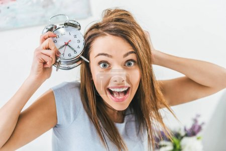 excited girl holding alarm clock and looking at camera