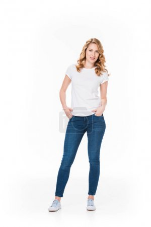 Photo for Smiling blond woman with hands in pockets looking at camera isolated on white - Royalty Free Image