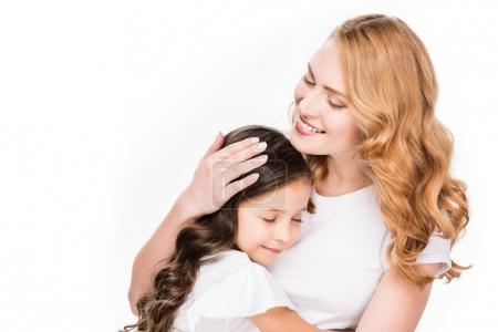 portrait of smiling mother hugging daughter isolated on white