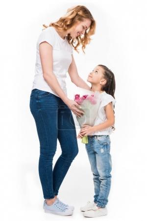 Photo pour Mère heureuse et petite fille avec bouquet de fleurs isolées sur blanc, concept de fête des mères - image libre de droit