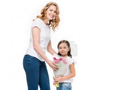 Photo pour Portrait de mère heureuse et petite fille avec bouquet de fleurs isolées sur blanc, concept de fête des mères - image libre de droit