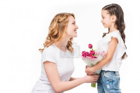 side view of happy mother and little daughter with bouquet of flowers isolated on white, mothers day concept