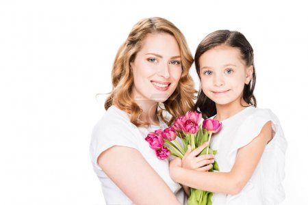 portrait of happy mother and little daughter with bouquet of flowers isolated on white, mothers day holiday concept
