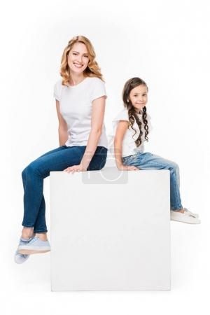 Photo for Mother and daughter sitting on empty white cube isolated on white - Royalty Free Image