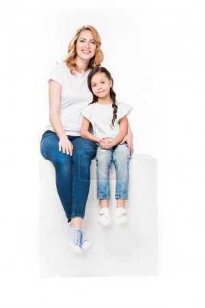 Photo for Mother hugging daughter while sitting on white cube together isolated on white - Royalty Free Image
