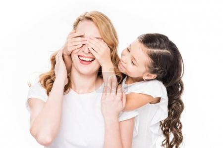 portrait of child covering eyes to smiling mother isolated on white
