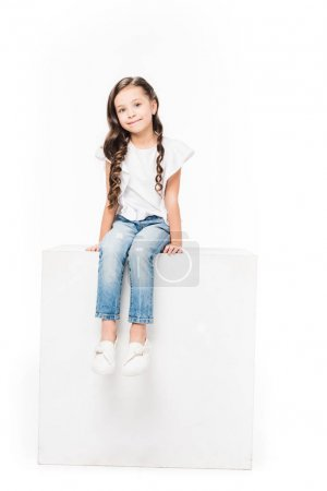 Photo for Smiling kid sitting on blank cube isolated on white - Royalty Free Image
