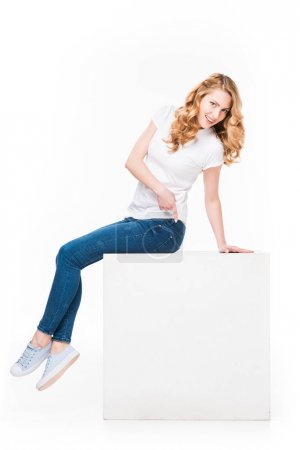 woman pointing at on empty white cube isolated on white