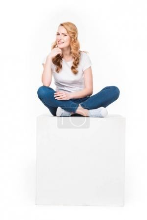 Photo pour Femme souriante assise sur un cube blanc vide isolé sur blanc - image libre de droit