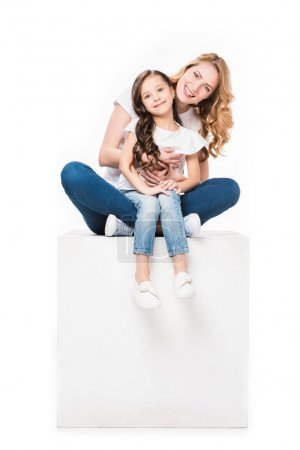 mother and daughter sitting on empty white cube isolated on white