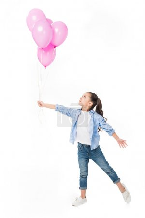 Photo for Adorable little kid looking at pink balloons in hand isolated on white - Royalty Free Image
