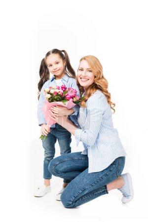 Photo pour Mère et petite fille souriantes avec bouquet de fleurs isolées sur blanc, concept de fête des mères - image libre de droit