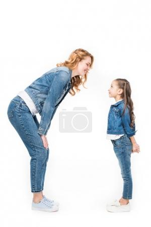 side view of family in denim clothing looking at each other isolated on white