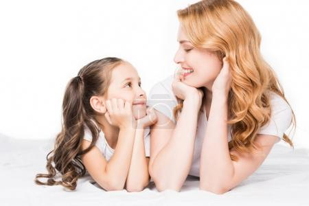 Photo for Portrait of smiling mother and daughter looking at each other isolated on white - Royalty Free Image