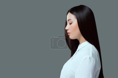 profile portrait of beautiful young asian woman standing isolated on grey