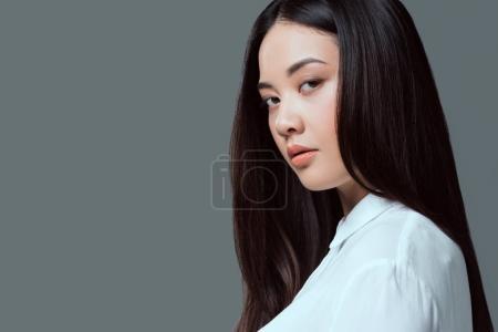 gros plan portrait de belle asiat regardant caméra isolée sur fond gris