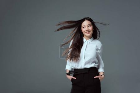 beautiful smiling asian girl standing with hands in pockets and looking away isolated on grey