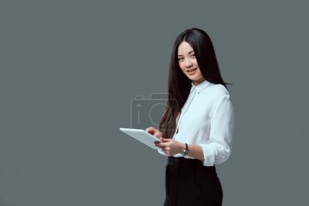 Photo for Smiling young asian woman using digital tablet and looking at camera isolated on grey - Royalty Free Image