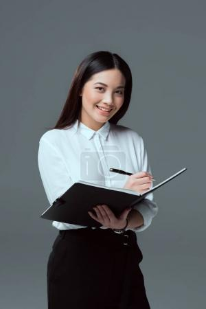 smiling young businesswoman taking notes and looking at camera isolated on grey