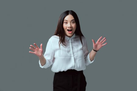 shocked young woman gesturing with hands and looking at camera isolated on grey