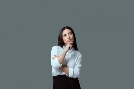 pensive young woman standing with hand on chin and looking away isolated on grey