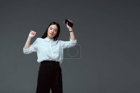 beautiful young woman in earphones listening music with smartphone and dancing isolated on grey