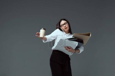 attractive businesswoman with folders and coffee to go talking by smartphone isolated on grey