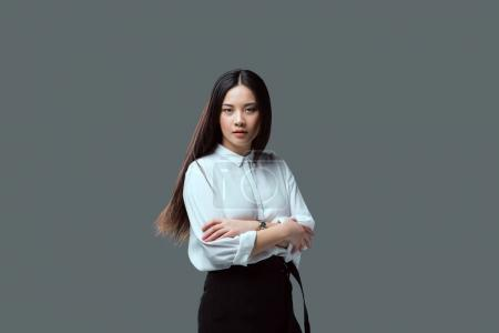 beautiful asian girl standing with crossed arms and looking at camera isolated on grey