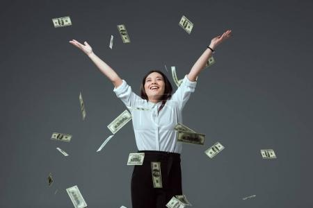 happy young asian woman throwing dollar banknotes isolated on grey