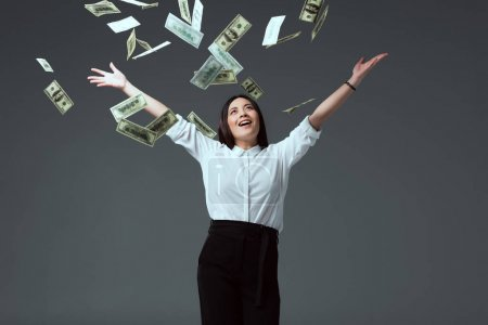 Photo for Smiling young woman throwing dollar banknotes isolated on grey - Royalty Free Image